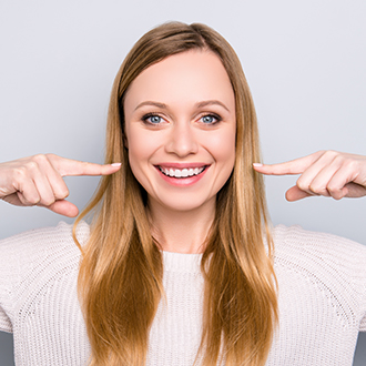 Woman pointing to smile after dental treatment